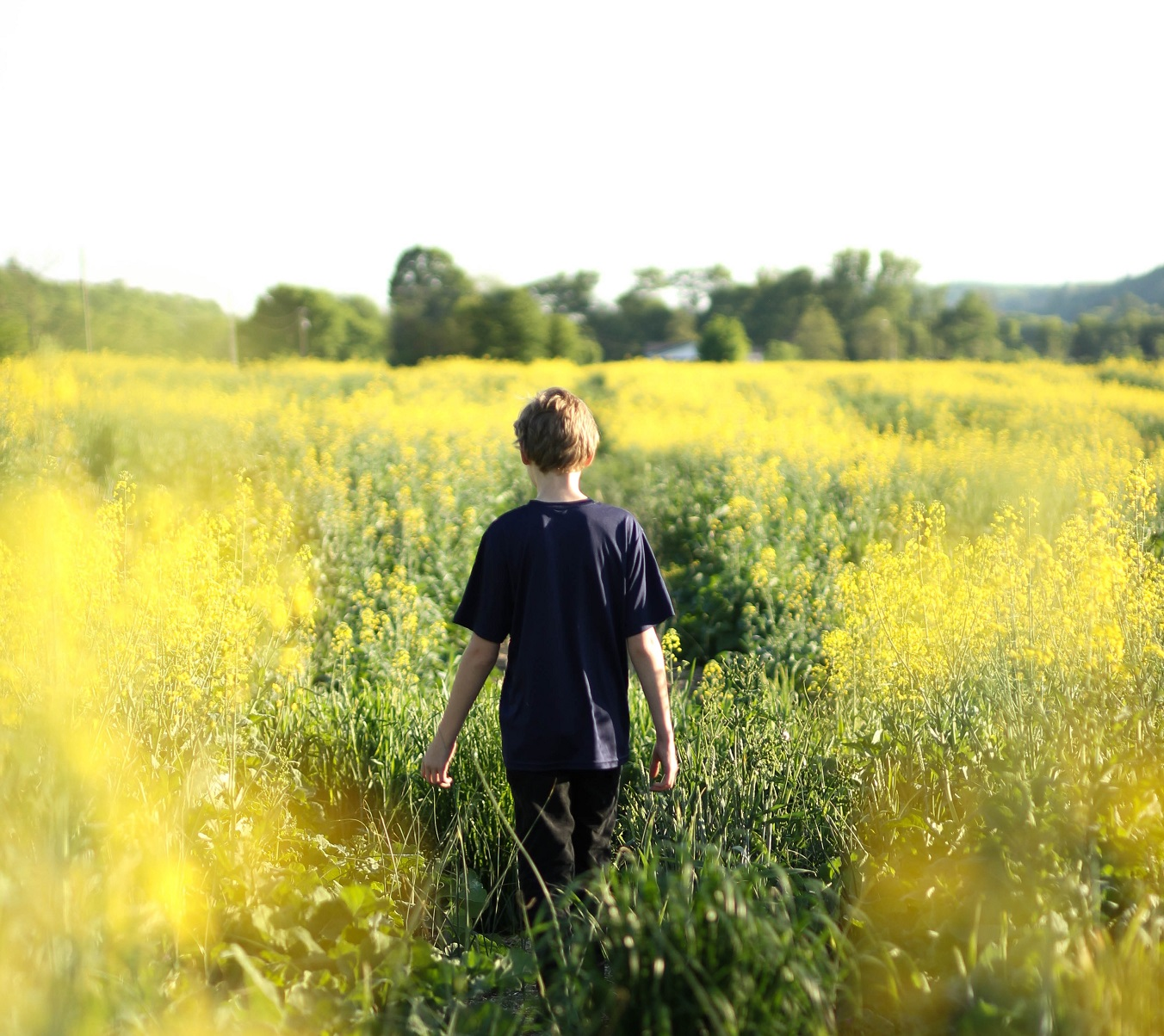 child walking through grass