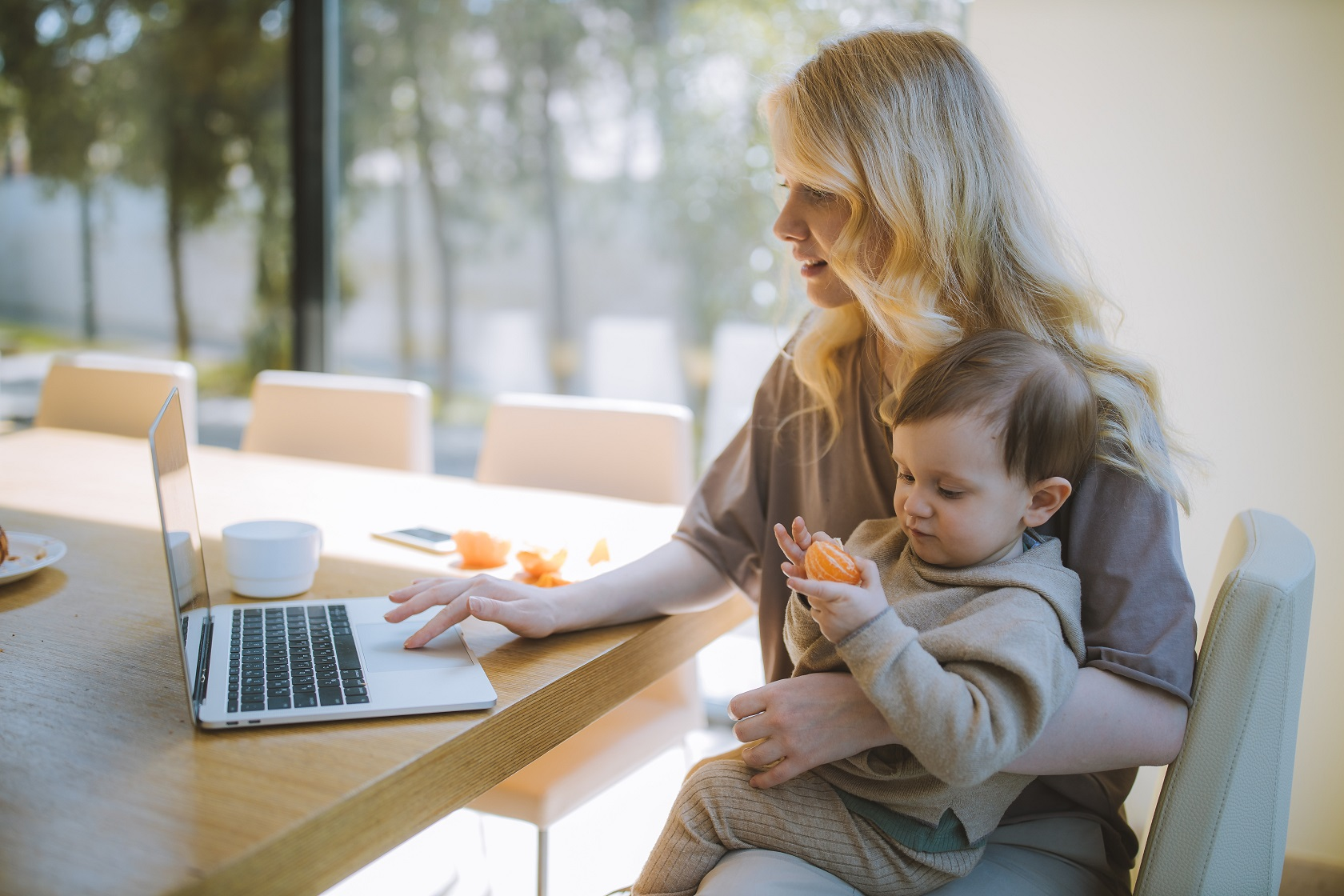 woman with child on lap doing work
