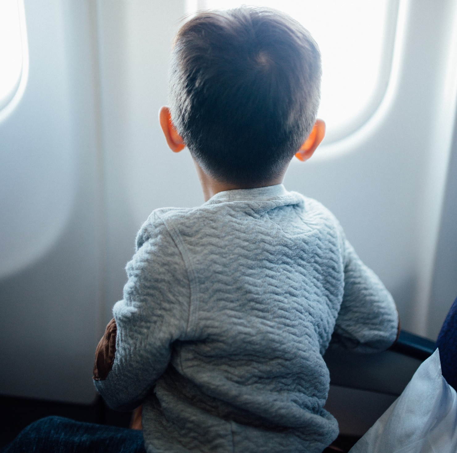 child looking out airplane window