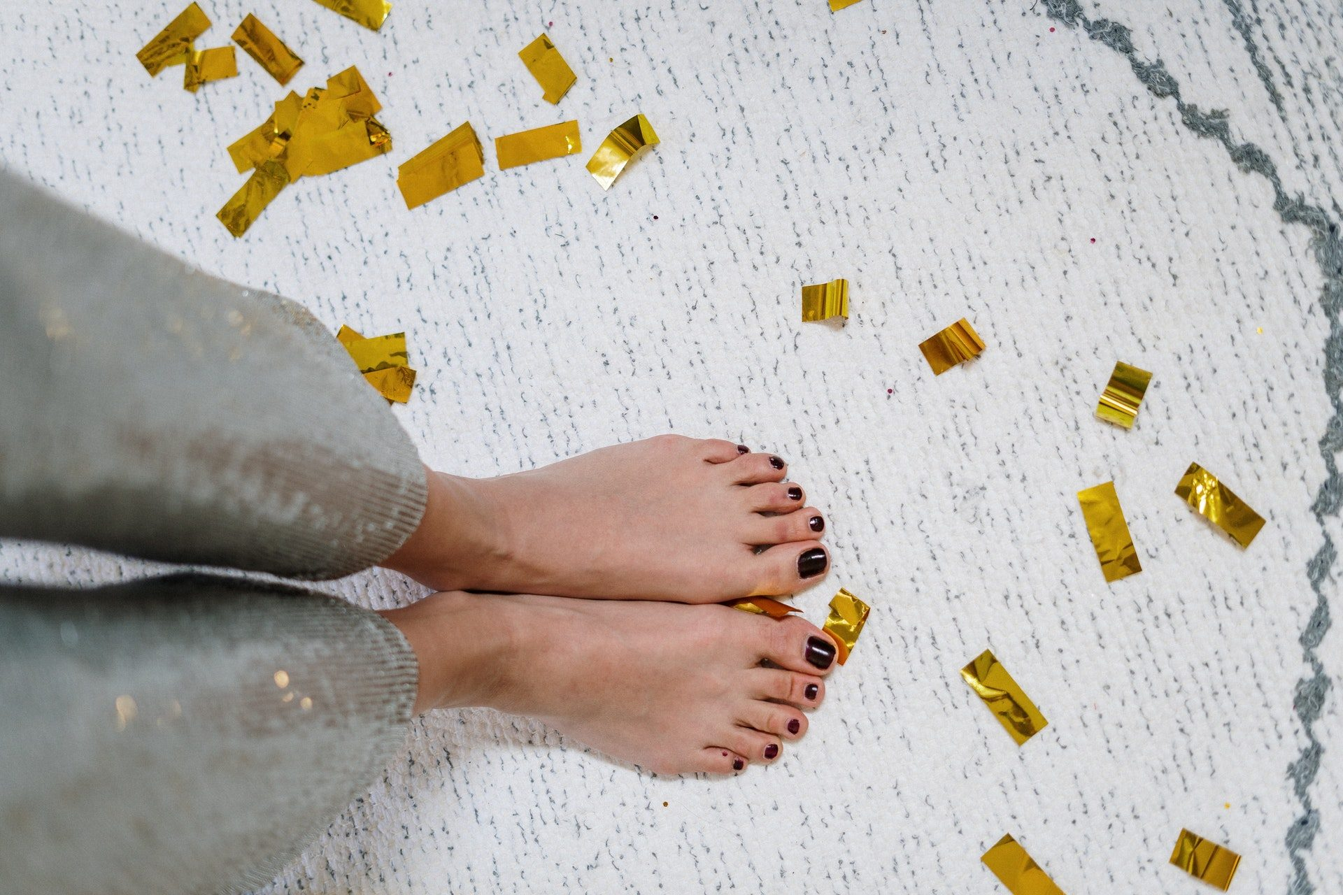 person with feet on rug and confetti